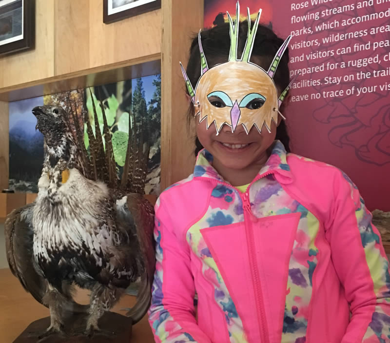 Student in a sage-grouse mask that she decorated; see the mask activity in the left column